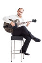 Musician on a stool well dressed jazz sitting and holding guitar Royalty Free Stock Photography