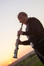 Musician trumpeter playing the instrument at sunset Stock Photography