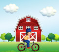 A muslim boy biking near the barnhouse illustration of Stock Images