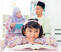 Muslim girl reading book malay family at home southeast asian parents and child living lifestyle Stock Photos
