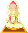 Muslim girl sitting on the prayer rug while praying