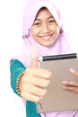 Muslim girl using tablet computer happy kid in head scraf and showing thumb up Royalty Free Stock Images