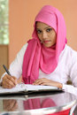 Muslim girls writing a diary book on the table Stock Photos