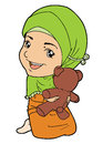 Muslim kid in head scarf playing with doll Stock Photography
