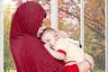 Muslim mother lull her baby at home portrait of wearing veil and near the window Royalty Free Stock Photos