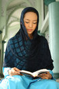 Muslim Woman at the Mosque Reading Qur'an Royalty Free Stock Photos