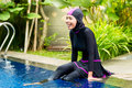 Muslim woman wearing Burkini swimwear at pool Royalty Free Stock Photo