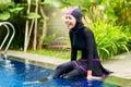 Muslim woman wearing burkini swimwear at pool or girl sitting in tropical garden halal Royalty Free Stock Photos