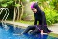 Muslim woman wearing Burkini swimwear at pool Royalty Free Stock Photo
