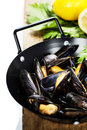 Mussels cooked with white wine sauce in a metal pot Stock Photo