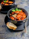 Mussels in tomato sauce with spaghetti in a dark plate. Mussels pasta. Mediterranean Kitchen. Vertical shot