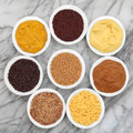 Mustard selection of powder seed french dijon english and wholegrain in white porcelain spoons over marble background Stock Photos