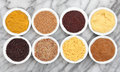 Mustard types selection of powder seed french dijon english and wholegrain in white porcelain bowls over marble background Royalty Free Stock Images