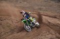 Mx motorcycle with rider shoots out of a turn racer on on sandy track Royalty Free Stock Photo