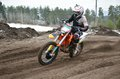 Mx motorcycle with rider shoots out of a turn racer on on sandy track Stock Photos