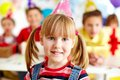 My birthday party joyful girl in cap looking at camera with her friends on background Stock Photography