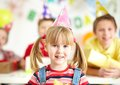 My birthday party joyful girl in cap looking at camera with her friends on background Stock Images