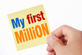My first million hand holding the yellow sticky note with text isolated on white background Stock Photography