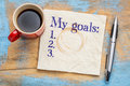 My goals list on napkin and coffee a stained against grunge wood table with a cup of Royalty Free Stock Image