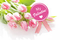 My valentine greeting card with a bunch of fresh pink tulips lying on a white background with a round pink rosette with a festive Stock Images
