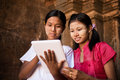 Myanmar girl using digital tablet pc portrait of two beautiful young traditional together Stock Image