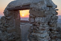 Mykonos sunset through stone gate on seen old with sea and island in background Stock Image