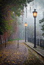 The mysterious alleyway in foggy autumn time with lighted lamps Stock Photo