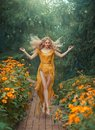 Mysterious attractive flower fairy in light yellow dress with long train and open legs in jump in the forest with bright Royalty Free Stock Photo