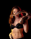 Mysterious beautiful exotic woman boa entwined around her body standing shadows dark background Stock Images
