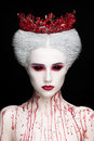 Mysterious beauty portrait of snow queen covered with blood. Bright luxury makeup. Black demon eyes. Royalty Free Stock Photo