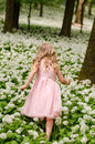 Mysterious blond princess in woods rear view child running fin green Royalty Free Stock Photos