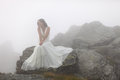 Mysterious bride sitting on rocky mountain top young woman in white dress stones surrounded by fog Royalty Free Stock Photo
