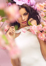Mysterious brunette woman with lots of flowers the pink Royalty Free Stock Photo