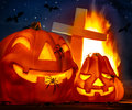 Mysterious halloween night glowing pumpkins with spiders on it cross near burning flame flying bat in dark starry fear Royalty Free Stock Photos