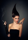 Mysterious lady in dark hood with cigarette woman Royalty Free Stock Photo
