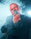 Mysterious man with red face smoking cigar. Stock Photo