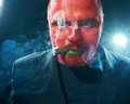 Mysterious man with red face smoking cigar. Stock Photography