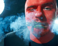 Mysterious man with red face smoking cigar. Royalty Free Stock Images