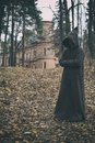 Mysterious monk, wizard or adept of secret society in hooded robe stands in forest against the background of medieval castle or Royalty Free Stock Photo