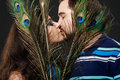 Mysterious stranger girl with long eyelashes passionately kisses a regular guy hiding behind peacock feathers attractive young Stock Photo