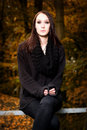 Mysterious woman sitting on a bench in the forest vertical portrait of beautiful young brunette wearing black clothes autumn Stock Photo