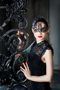 Mysterious woman in venetian carnival mask near wrought iron gate Royalty Free Stock Photo