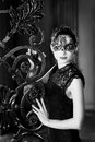 Mysterious woman in venetian carnival mask near wrought iron gate. Noir style Royalty Free Stock Photo