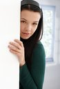 Mysterious young female hiding behind wall Royalty Free Stock Images