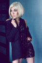 Mysterious young woman in jacket and lace scarf beautiful with short blond hair black Stock Photography