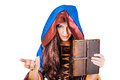 Mystery young halloween witch and old magical book beautiful wearing vintage gothic dress with hood holding of spells in leather Stock Image