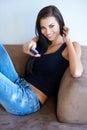 Nätt kvinna på hållande avlägsen kontrollant för soffa Arkivbild
