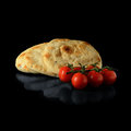 Naan bread stacked warm indian breads with dew covered tomatoes against a black background with soft reflections copy space Stock Images