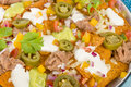 Nachos cheesy topped with sour cream refried beans pico de gallo jalapenos and guacamole Stock Photography