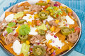 Nachos cheesy topped with sour cream refried beans pico de gallo jalapenos and guacamole Stock Photos